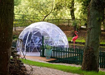 Geodesic dome overlooking the pond is accessed via a gently sloping gravel path.