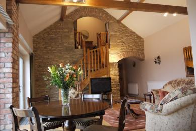 Feature stone wall, stairs to mezzanine and archway to kitchen.