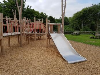 Play equipment includes a double width slide