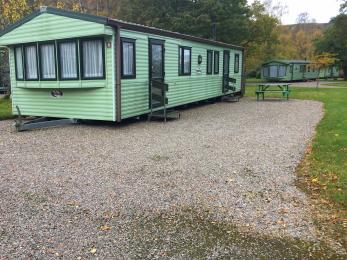 Standard 3 bed caravan showing level gravelled parking plus picnic bench next to caravan