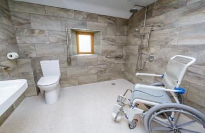 Wet room with self propelling shower/commode chair