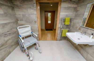 The wet room has wheelchair accessible basin with hand grips on both sides.