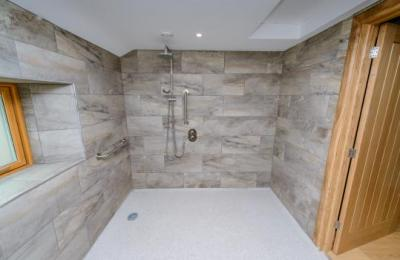 The wet room shower has two heads, one fixed overhead and one hand held, with grab rails on both sides of the shower bar.