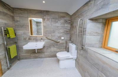 Wet room with accessible basin, comfort height (48cm) toilet, backlit mirror, large window with frosted glass and heated towel ladder.
