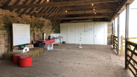 A picture of the inside of the shed. Concrete floor, toilets at one end.