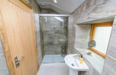 En suite to double bedroom; shower measures 1200x800mm with sliding door and storage for toiletries.