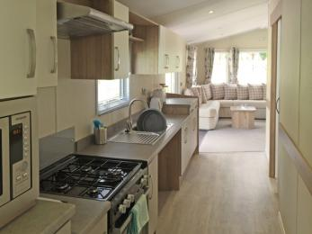 Accessible Caravan open plan galley kitchen has accessible height surfaces