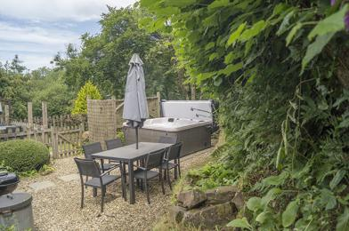 Private gated garden with patio furniture and hot tub