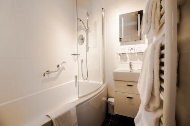 Aston's en suite has a bath with shower over.