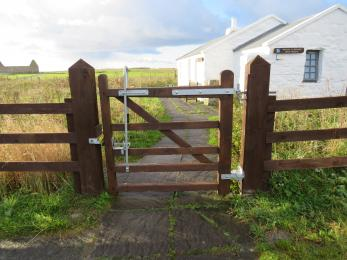 A wide wooden gate with a two-way opening hinge is the opening between the parking area and the visitor centre.