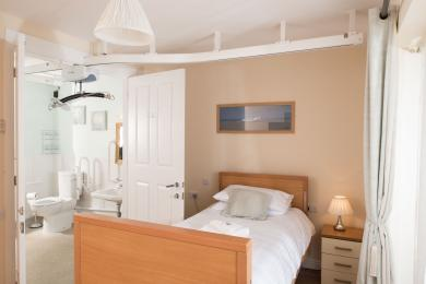 Bedroom with ceiling tracking leading to ensuite wetroom