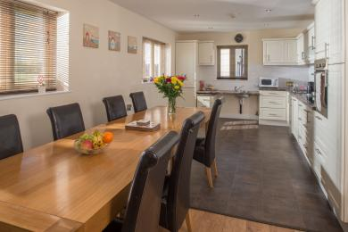 Dining table and chairs for 8 people in open plan kitchen dining layout