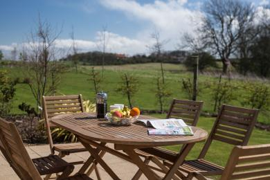 Patio table and chairs with shrubland views
