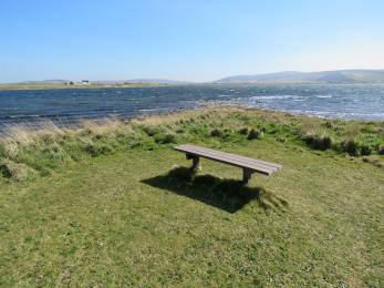 Bench by shores of Loch of Stenness on Brodgar nature reserve footpath