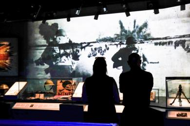 A couple stand in front of an audio visual display in the main exhibition area. They are in shadow as there is low lighting.