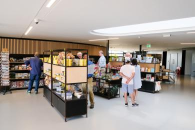 The museum shop area. There are free standing shelving units with room to fit two wheelchairs between them.