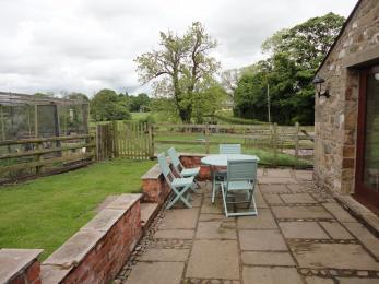 Patio with grass area behind The Granary adjacent to the vegetable garden