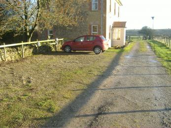 View of Graveled car park and driveway to house.
