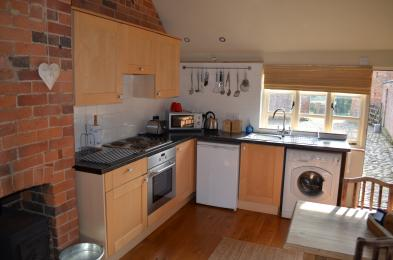 Kitchen with hob, oven, sink, fridge, cupboards and work tops.