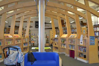 This photo shows the Story Place, a seated area under a wooden arch filled with children's books.