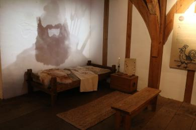 View of Lesser Chamber, including a replica bed and dream projection.