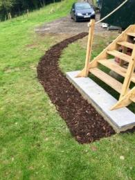 Pathway to shepherd's hut onto concrete surface and 5 steps up to the entrance.