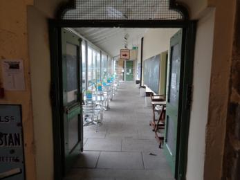 Glass corridor indoor picnic area showing tables and chairs