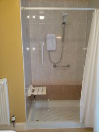 Ground floor bathroom shower with flap seat lowered and showing two grab rails