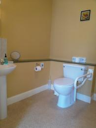 Groud floor bathroom toilet with assistance rail lowered