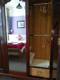 Wardrobe in ground floor bedroom with door open to show low level clothes hanging rail
