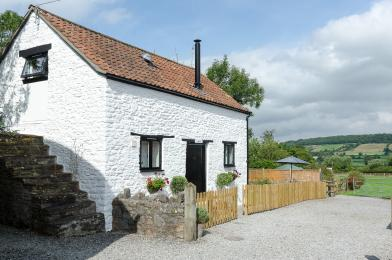 Hayloft Cottage showing garden fence and parking area adjacent on loose gravel and a slight slope