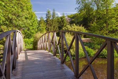 A wooden bridge across a stream to an unpaved path through dense foliage.