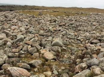 Photo shows the widest boulder beach, which is strewn with boulders of varying sizes. A faint path has been created for ease