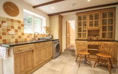 Second view of Hollowtree cottage kitchen showing washing machine and entrance to bathroom suite