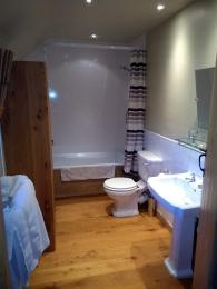 Bathroom showing bath/shower, toilet, basin and towel rail.