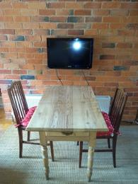 TV wall mounted next to the table and chairs.