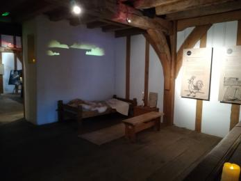 A bed with a bench nearby sits beneath a movie that is projected on the wall in the Lesser Chamber.