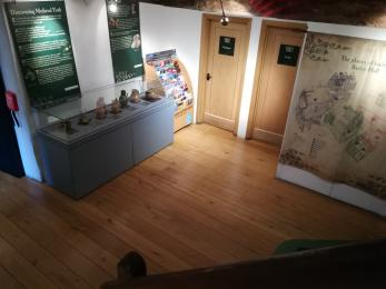 The Vestibule, which includes a large tapestry on the wall and a low cabinet of Medieval artefacts.