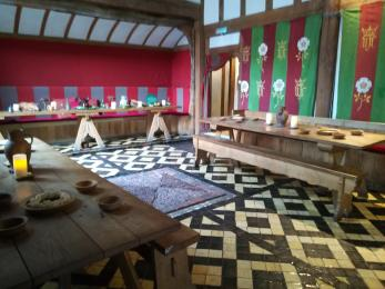 Long wooden tables and benches are arranged on a tiled floor in the Great Hall.