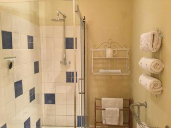 Walk in shower, towel storage and traditional radiator opposite. Shelves and additional towel rail.