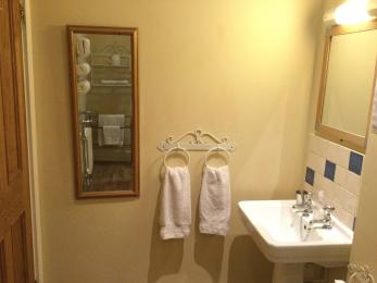 Washbasin with shaver point and light above, hand towel rails and full length mirror