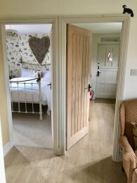 The majority of walls around door frames are light coloured, the doors themselves are natural wood (except for the internal entrance door which is a similar painted colour to the kitchen walls).