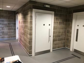Accesible toilet in hallway. Door is side-hung and opens left.