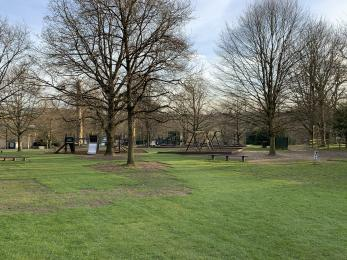 A wooden playground with grassy area in front. There are some benches and trees.