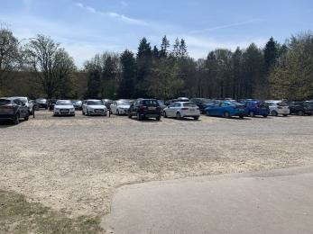 Rows of cars parked on a low slope with a gravel surface. There are trees lining the carpark.