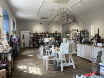 The interior of the shop. There are several tall shelves around the walls of the room and tables the middle.