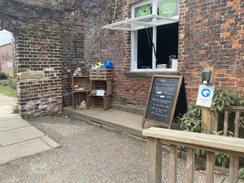 A refreshment kiosk servery that uses a window in a brick building. There is a step up to the serving window.