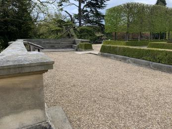 A section of the terrace. The ground is gravel and there is a small wooden ramp going over a step.