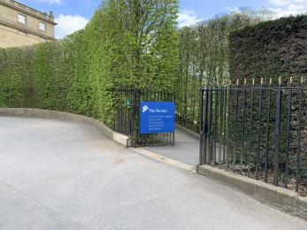 A gate through to the terrace. There is a gentle slope beyond the gate through to some hedges.
