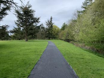 The path on the North Park. A plastic tracking path cuts across a grass field with trees either side.